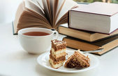 Cup of tea, cake and some books to read lying on the table — Stock Photo