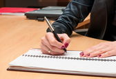 Woman writes something on a white paper. Office work — Stockfoto