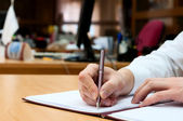 Man writes something on a white paper. Office work — Стоковое фото