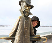 Beautiful red-haired girl standing on the waterfront next to the statue of Anton Chekhov — Stock Photo
