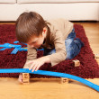 Little boy is building toy railroad using bricks - Stock Photo