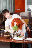 "Young pair on the kitchen: bring her ""flowers"" — Stock Photo"