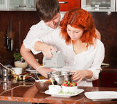 Young pair on the kitchen: making pastry together — Stock Photo