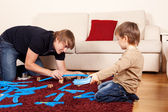 Father is playing with son in toy railroad — Stock Photo