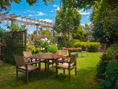 Dining table set in lush garden — Stock Photo