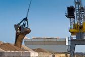 Harbor crane unloading ship — Stock Photo