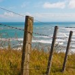 Seascape over fence - Stock Photo