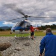 Tourist boarding helicopter - Stock Photo