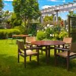 Dining table set in lush garden — Stock Photo #34020369