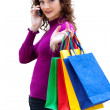 Young woman with color bags and mobile phone — Stockfoto