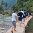 Stock Photo: Tourists walk on the bridge. Vang Vieng. Laos.