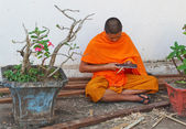 Buddhist Monk works with a knife and wood. Luang Prabang. Laos. — Stock Photo