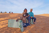 Unidentified Vietnamese young boys with Sandboards for tourists on Red Sand dunes. Mui Ne. Vietnam — Stockfoto