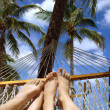 Stock Photo: Feet of man and woman lying in the sun under the palm trees in a hammock.