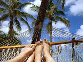 Feet of man and woman lying in the sun under the palm trees in a hammock. — Stock Photo