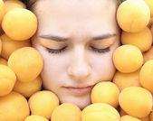 Girl's face and apricots — Stok fotoğraf