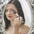 Girl making makeup in the mirror — Stock Photo