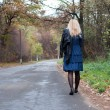 Beautiful girl walking away on a road in Autumn — Stock Photo