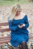красивая девушка с мобильного телефона в парке в осень — Стоковое фото