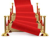 Red carpet rolling down the stairs — Stock Photo