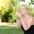 Beautiful blond woman painting her lips in the park — Stock Photo