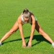 Attractive young woman doing stretching exercises on grass before run — Stock Photo