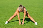 Atrakcyjna młoda kobieta robi ćwiczenia rozciągające na trawie przed uruchomić — Zdjęcie stockowe