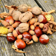Chestnuts, walnuts and hazelnuts on wooden background — Stock Photo