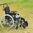 Empty wheelchair on meadow — Stock Photo #41779487