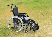 Empty wheelchair on meadow — Stock Photo