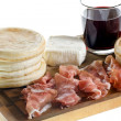 Cutting board with small round flat bread, ham, cheese and glass of red wine, typical dish of Emilia-Romagna — 图库照片
