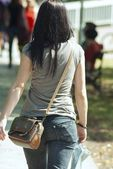 Woman walking in city park at sunny day — Stock Photo