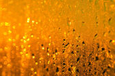 Wet yellow - gold glass background with drops and sparks — Stok fotoğraf