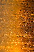 Wet yellow - gold glass background with drops and sparks — Stock Photo