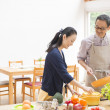 Husband and wife cooking together - Stock Photo