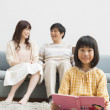 Japanese girl and her parents in living room - Stock Photo