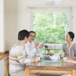 Japanese family in dining room - Stock Photo