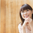 Japanese woman with wooden background - Stock Photo