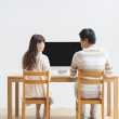 Young Japanese couple facing a computer display - Stock Photo