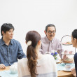 Japanese family having chat at dining table - Stock Photo