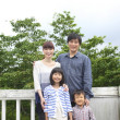 Japanese family at a deck in woodland - Stock Photo
