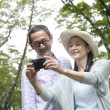 Senior Japanese couple taking picture with a digital camera - Zdjcie stockowe