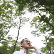 Senior Japanese man listening carefully in woods - Stock Photo
