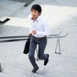 Japanese businessman running up the stairs - Stock Photo