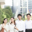 Group of Japanese businessmen outside office building - Stock Photo
