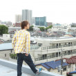 Japanese man glancing over the town from the rooftop - Stockfoto