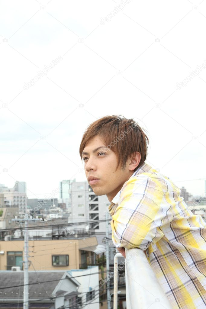 Japanese man glancing over the town from the rooftop — Stock Photo #15008707