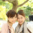 Japanese women taking their own picture using digital camera - Stockfoto