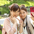 Japanese women taking their own picture using cell phone - Stock Photo