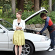 Japanese couple having engine failure trouble - Stock Photo
